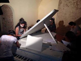 Studenti della Horcynus Summer School a lavoro sui pianoforti di Isgrò
