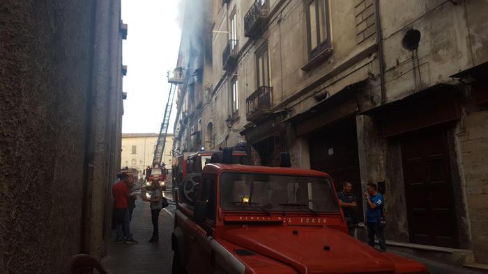 Vigili del fuoco al lavoro sull'incendio che si è sviluppato in un appartamento di uno stabile nel centro storico di Cosenza, 18 agosto 2017.